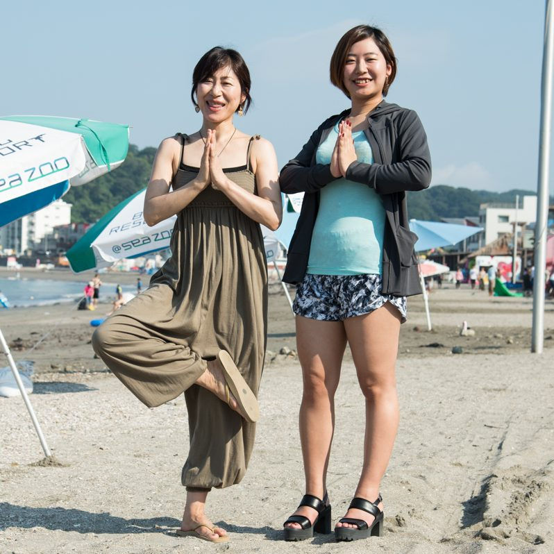 ビーチでヨガのポーズをする津下恵子さん、佐藤みのりさんの全身