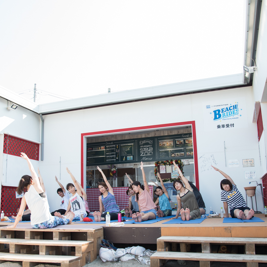 『Yoga Trip -Beach session-』で座りながらヨガを行うインストラクターと生徒たち