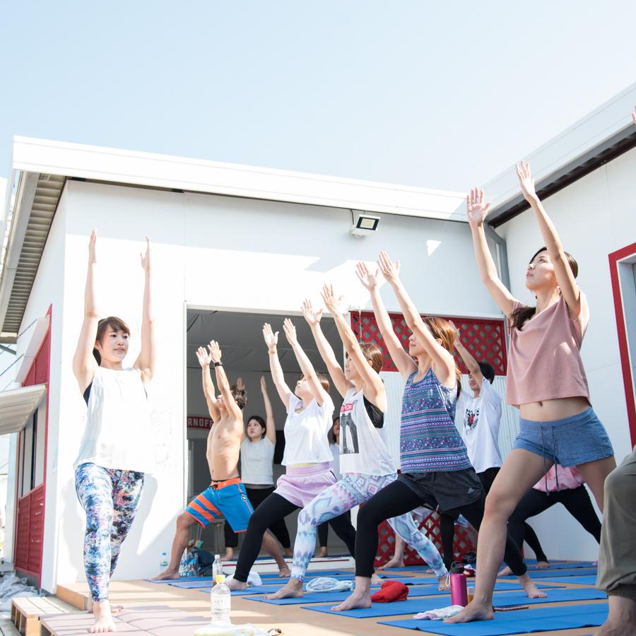 「Yoga Trip -Beach session-」の様子。ヨガを指導するインストラクターと生徒たち