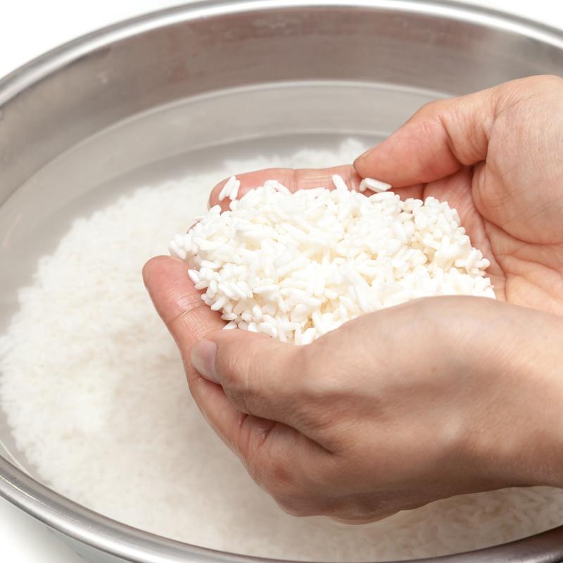 ボウルに入ったお米を両手ですくい上げている