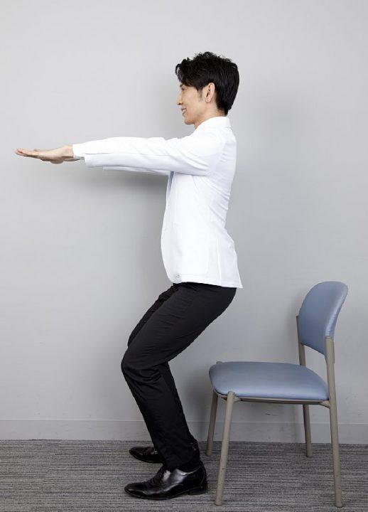 手を伸ばして椅子に座る途中
