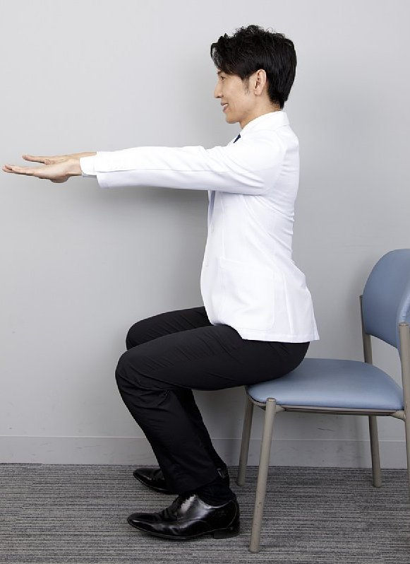 「7秒かけて座るだけダイエット」のやり方を説明する工藤孝文さん。横からの立った姿で両膝を曲げ、前に両手を伸ばしている