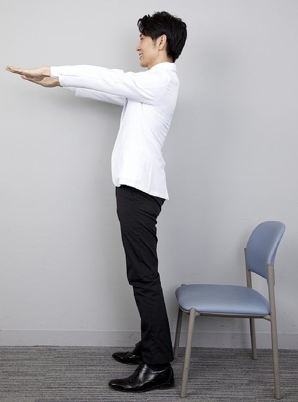 「7秒かけて座るだけダイエット」のやり方を説明する工藤孝文さん。横からの立った姿で前に両手を伸ばしている
