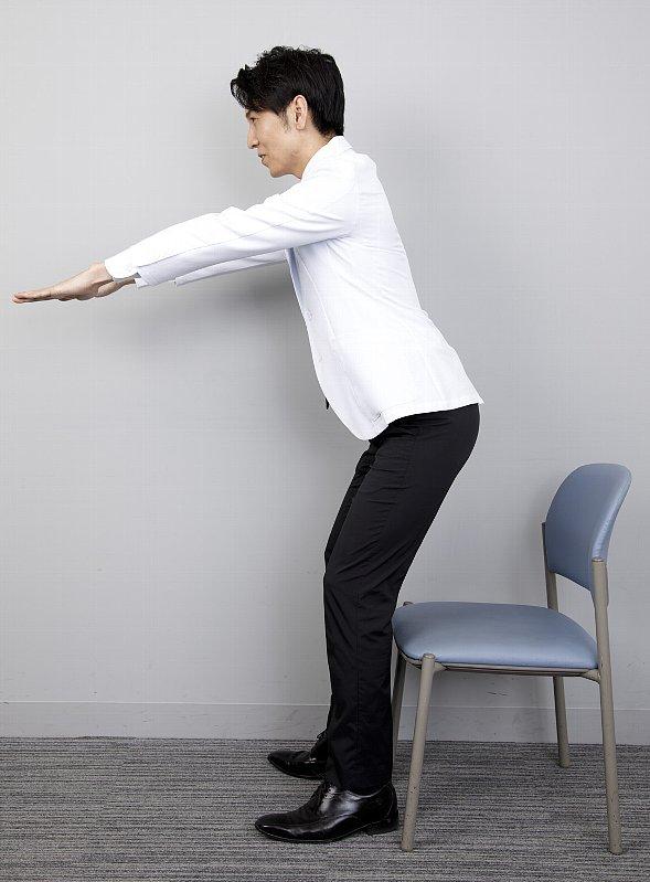 「7秒かけて座るだけダイエット」のやり方を説明する工藤孝文さん。横からの立った姿で前に前に伸ばした両手が下がっているNG姿勢