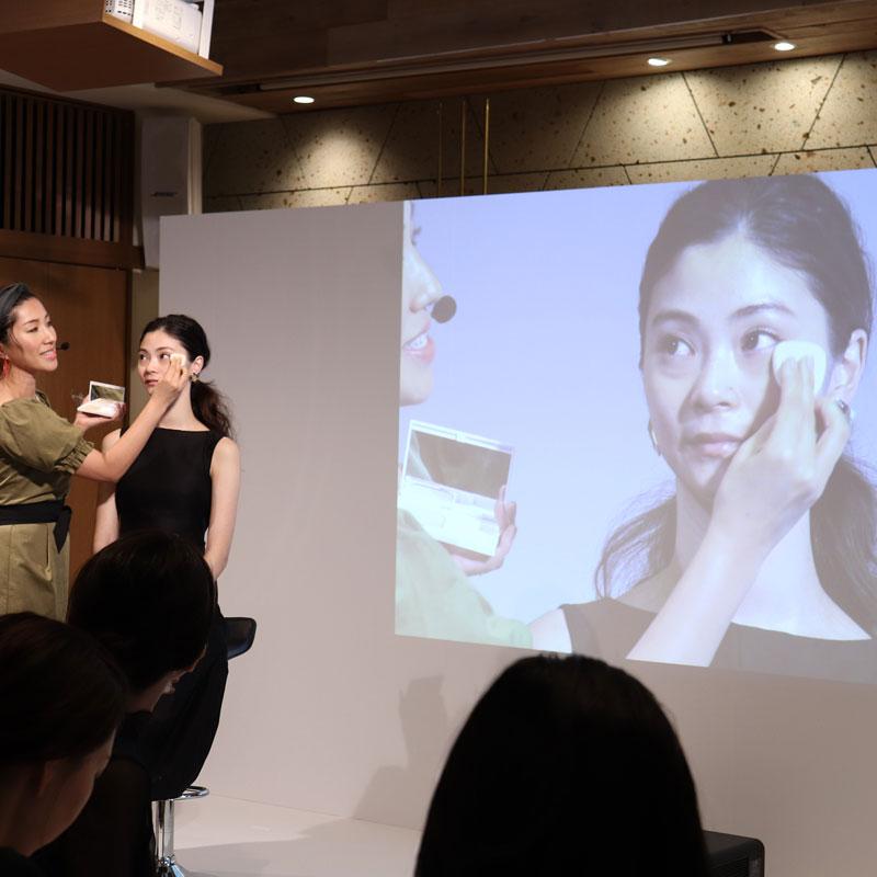 コフレドールの「ヌーディカバーモイスチャーパクトUV」を使ってモデル女性にベースメイクをレクチャーする、ヘア&メイクアップアーティストの長井かおりさん。モニターにはその映像も映し出されている