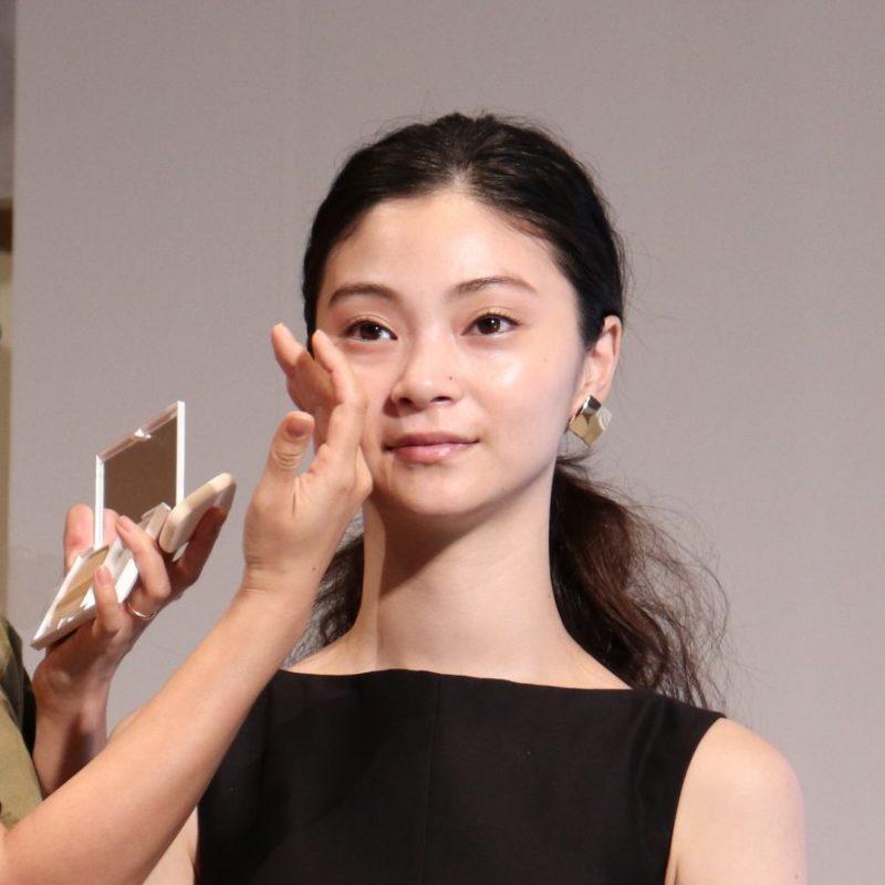 ヘア&メイクアップアーティストの長井かおりさんによって肌の様子をチャックされているモデル