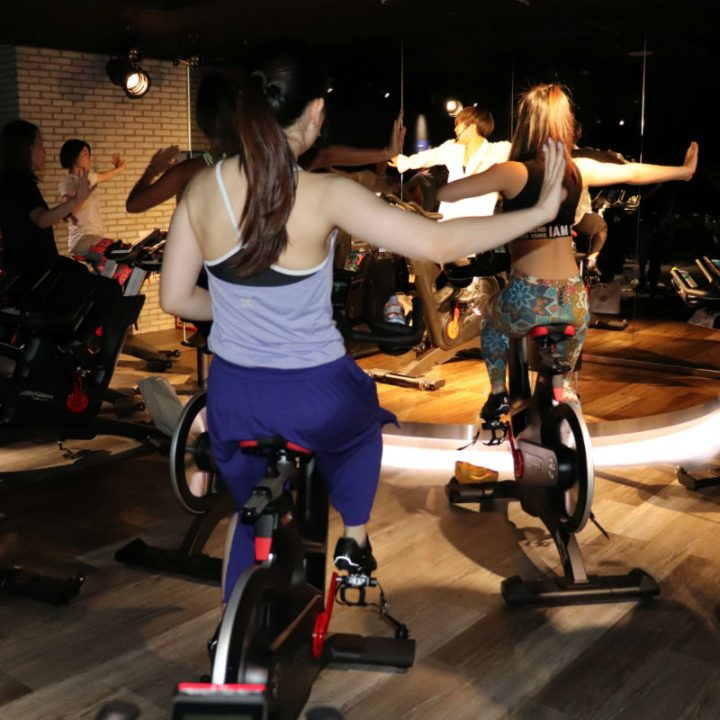 バイクに乗り、腕を広げる女性たち