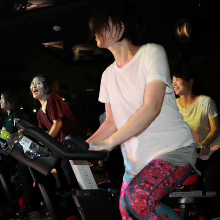 バイクをこぐ、白いTシャツの女性