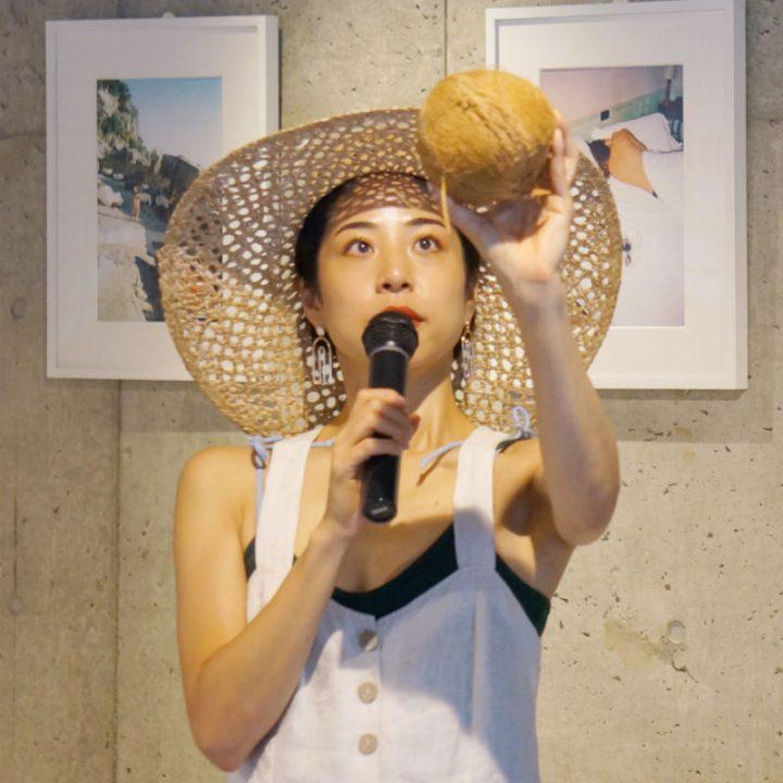 ココナッツを掲げる、麦わら帽子の福本敦子さん