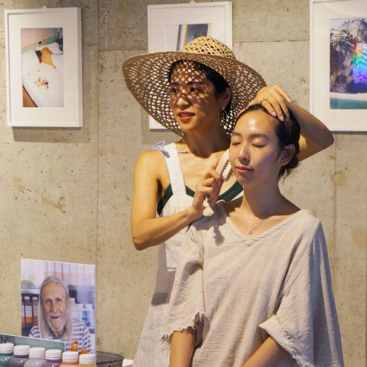ブラシを使って、モデルの顔を撫でる麦わら帽子の福本敦子さん