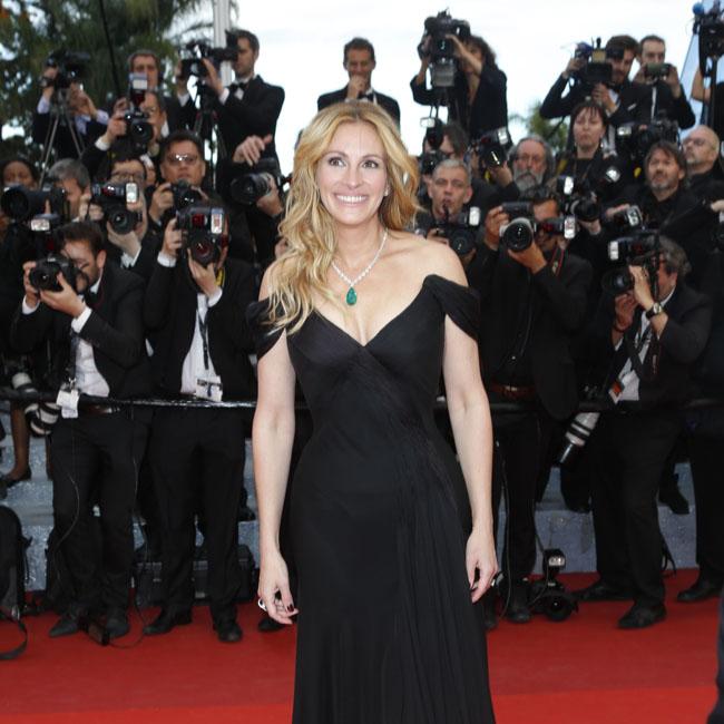 カメラのフラッシュがたかれる中、黒いドレス姿で立つジュリア・ロバーツ