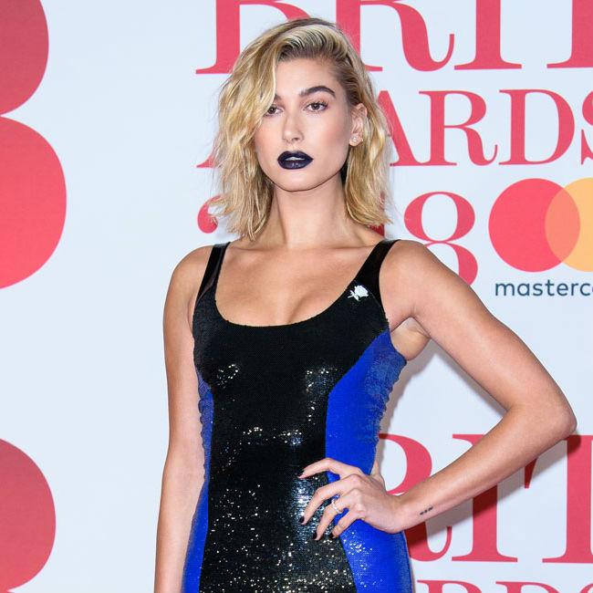 パネルの前に立つ、黒と青のドレスを着たヘイリー・ボールドウィン