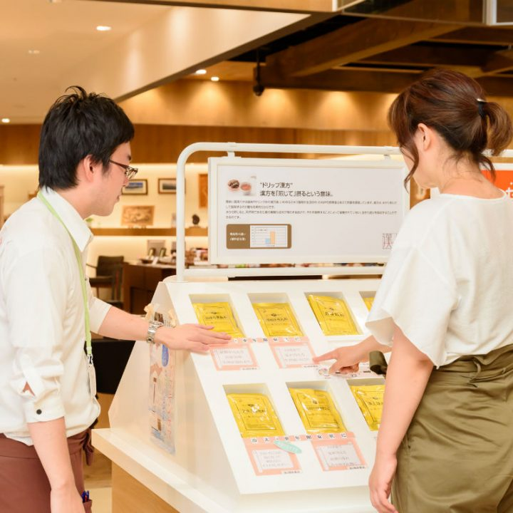 『KAMPO煎専堂』で漢方の棚の前で男性スタッフから説明を受ける女性