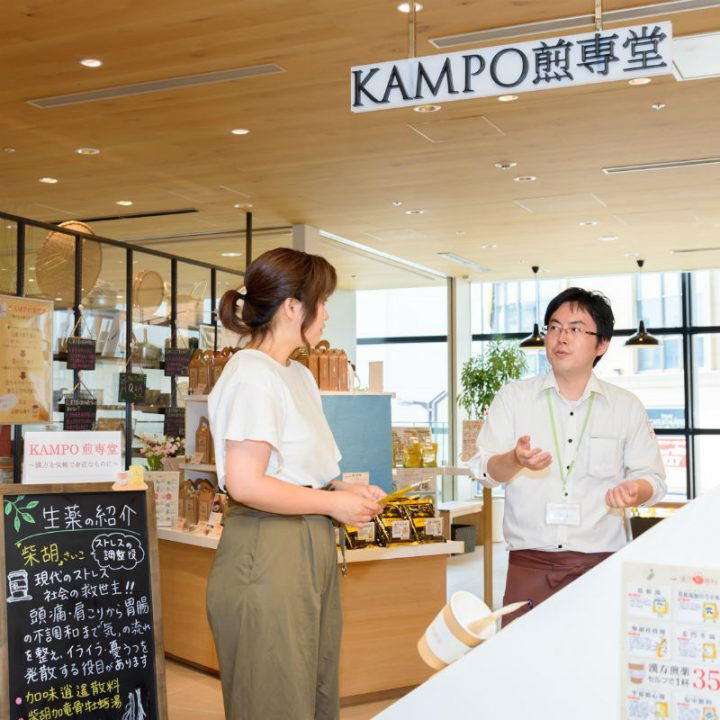 「KAMPO(カンポー)煎専堂」の店頭で男性スタッフから説明を受ける女性
