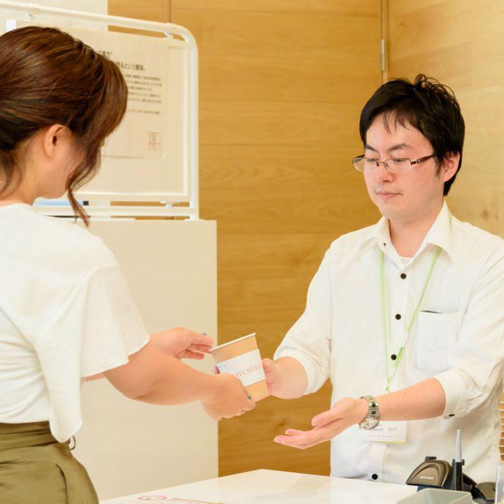 『KAMPO煎専堂』のレジで紙コップを受け取る女性
