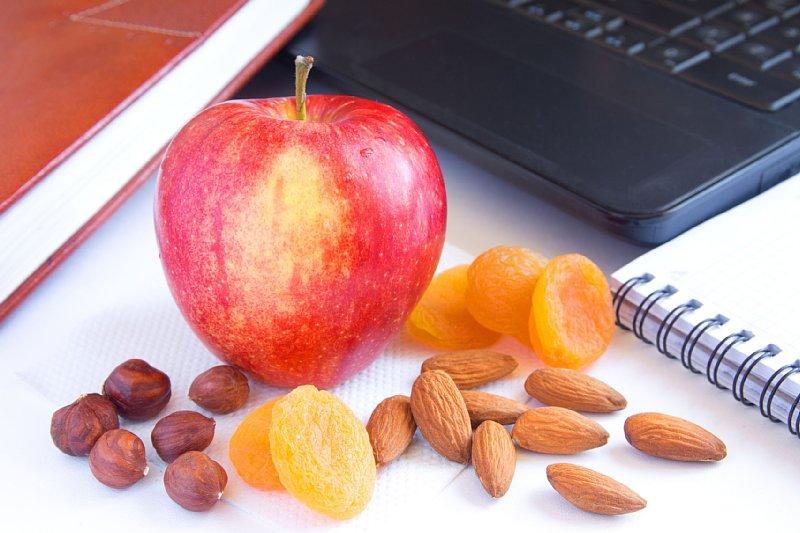 パソコンの横に置かれたりんご、アーモンド、ドライフルーツ
