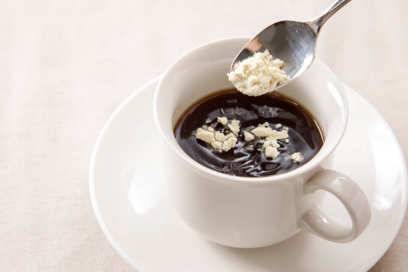 コーヒーにスプーンでおからパウダーを入れる