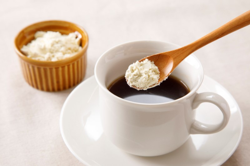 コーヒーにおからパウダーをスプーンで入れている