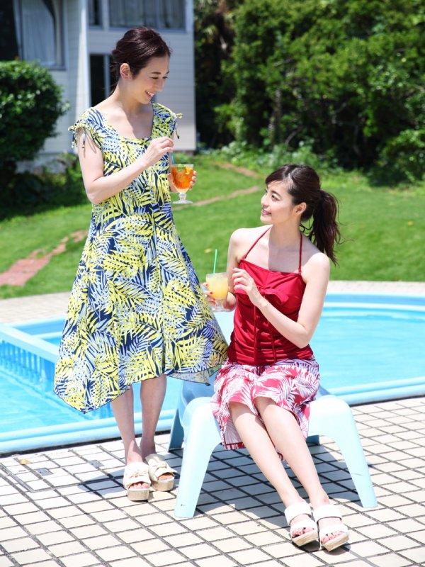 ビーチでドリンクを飲む水着姿の女性2人