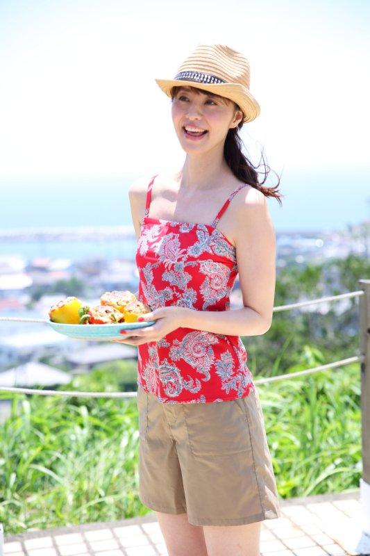 バーベキューの野菜のお皿を持ったペーズリー柄のタンキニ姿の女性