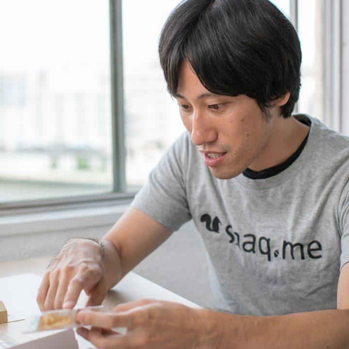 お菓子を指さして説明するグレーのTシャツを着た「snaq.me」代表取締役の服部慎太郎さん
