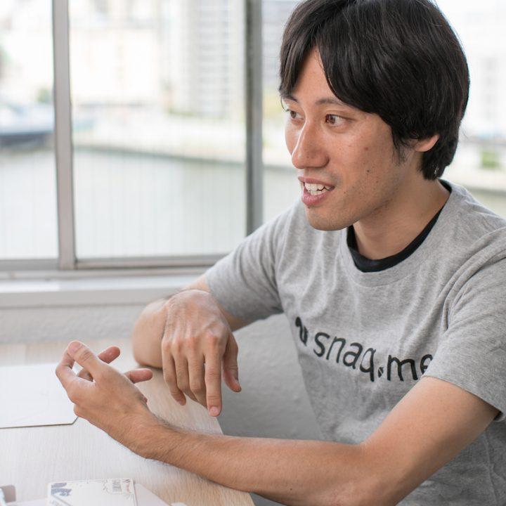 スマートフォンを操作するジェスチャーをする「snaq.me」代表取締役の服部慎太郎さん