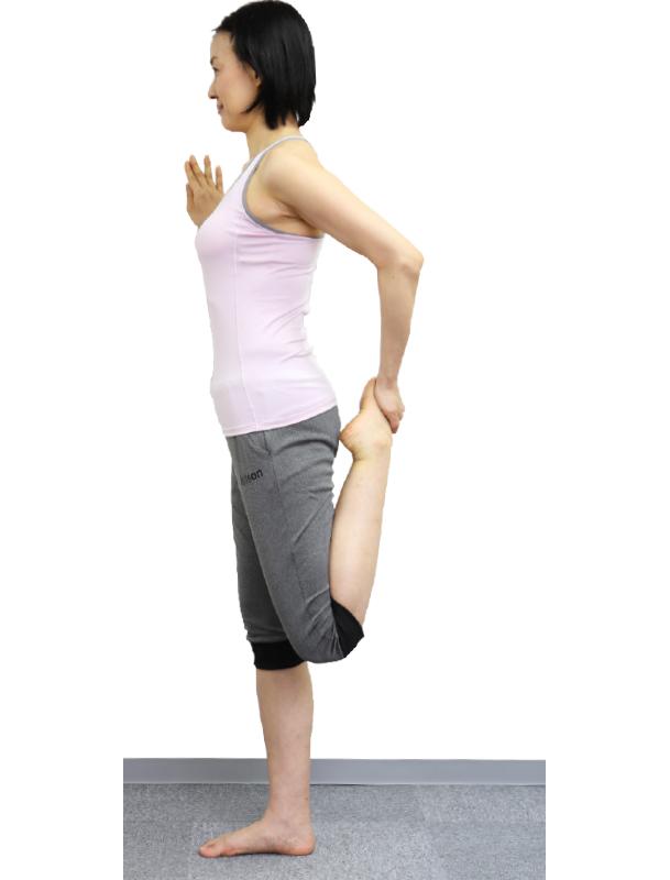 トレーニングウエア姿の女性が左手で左足の甲を持ち、かかとをお尻にスーッと寄せる