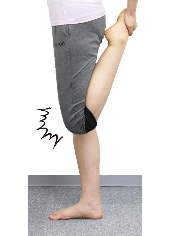 トレーニングウエア姿の女性が足の甲を持ちかかとをお尻に寄せている