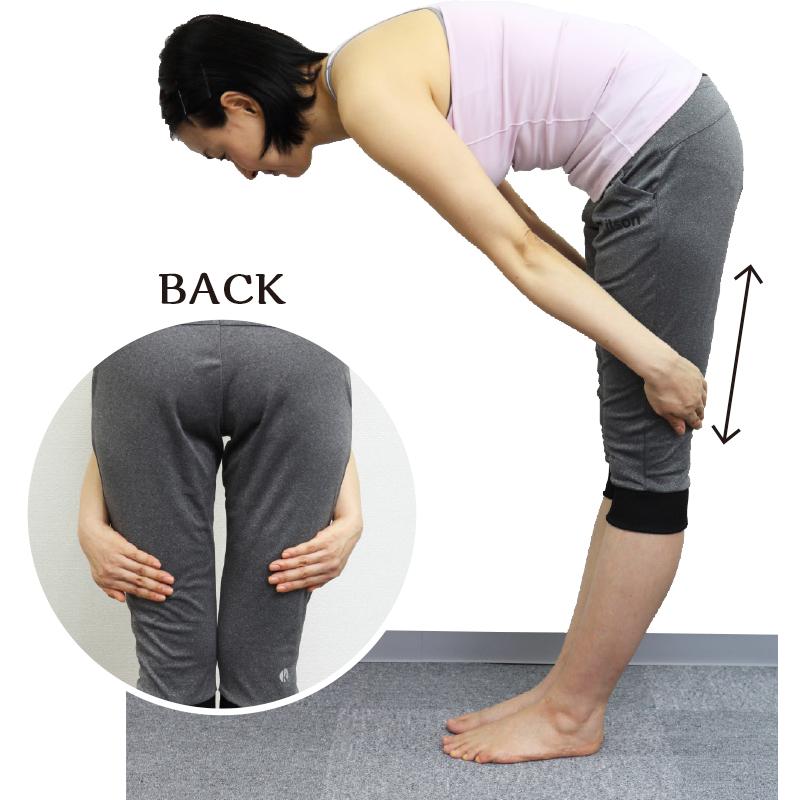 トレーニングウエア姿の女性が両足を閉じて立ち、太ももの真ん中から下を指の腹で上下にこする