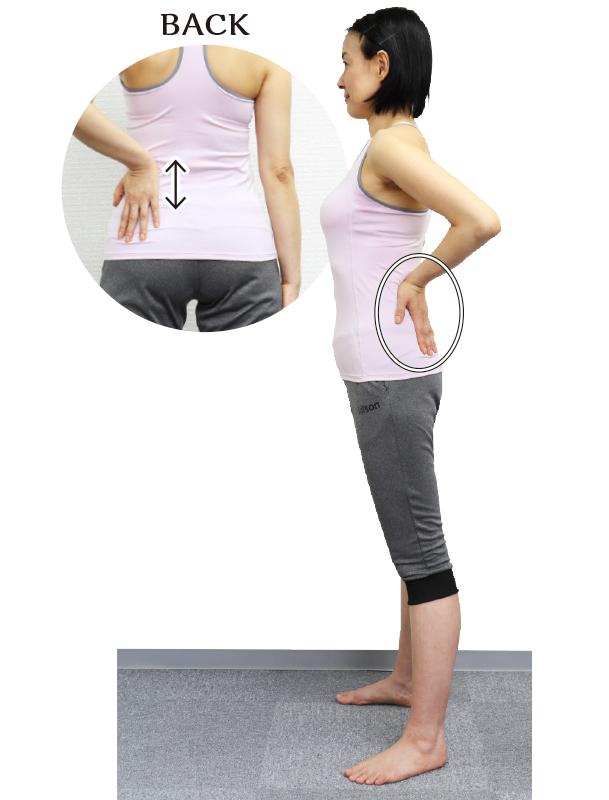 トレーニングウエア姿の女性が左腰骨の横の筋肉を、左手の親指の付け根で上下にこする