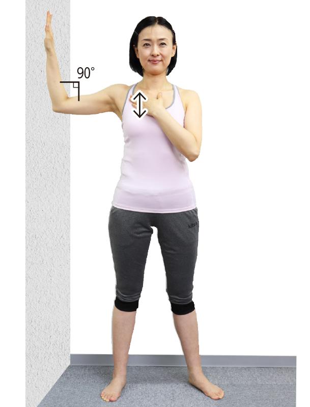 トレーニングウエア姿の女性が右手を肩の高さで直角に曲げて壁につけ、両足を肩幅よりやや広めに開いて立つ。右の鎖骨の下の筋肉を左手の指の腹で5回こする