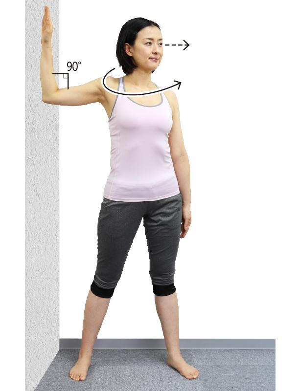 トレーニングウエア姿の女性が息を吐きながら上半身を左にひねる