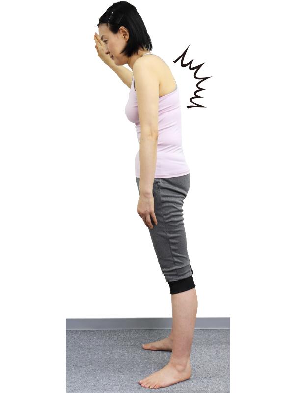 トレーニングウエア姿の女性が背中を丸めながら上半身を前に傾けている