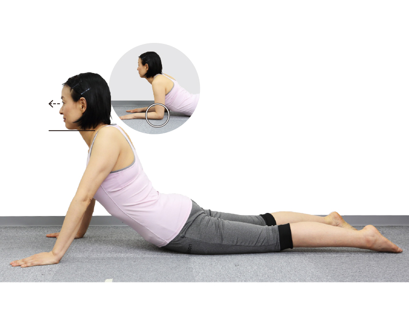 トレーニングウエア姿の女性がうつ伏せになり顔を正面に向け、両腕を伸ばして体を反らす