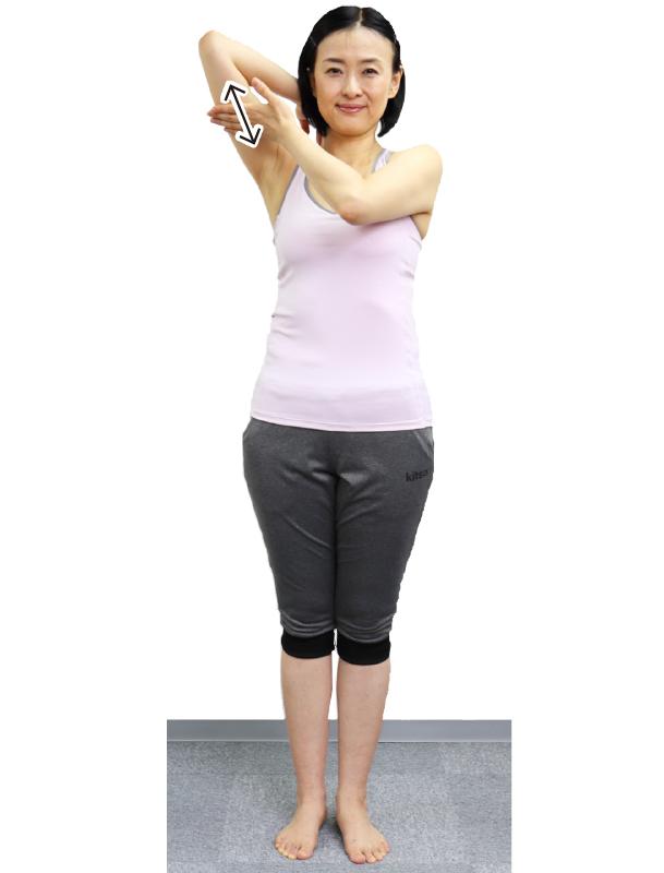 トレーニングウエア姿の女性が右手を後ろに曲げて、右手の二の腕裏側の真ん中を左手の指の腹で上下にこする