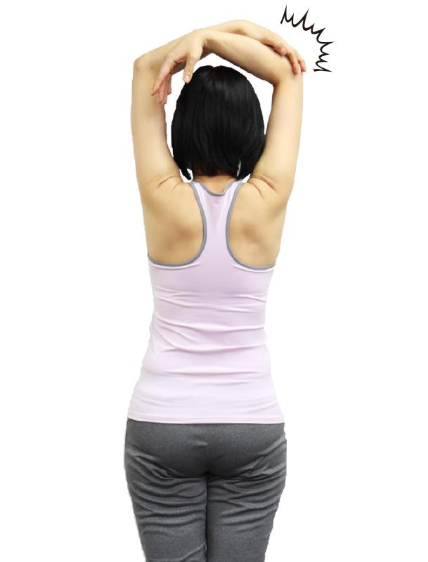 トレーニングウエア姿の女性が二の腕を伸ばそうとしているが、ひじしか曲がっていない