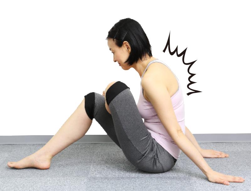 トレーニングウエア姿の女性が左手も床に置き、息を吐きながら右足を胸に近づけるが、背中が丸まっている