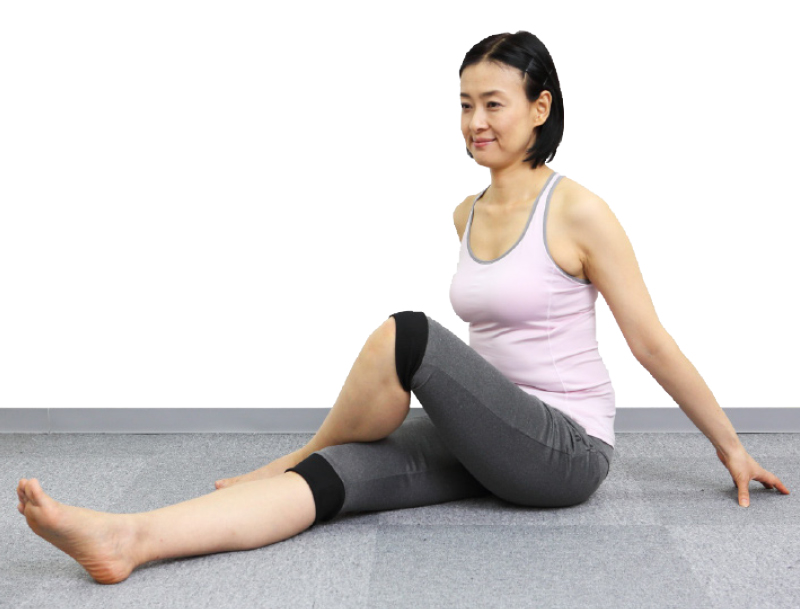 トレーニングウエア姿の女性が両足を出して床に座り、両手を後ろに置く。左ひざを立てて右ひざにかける