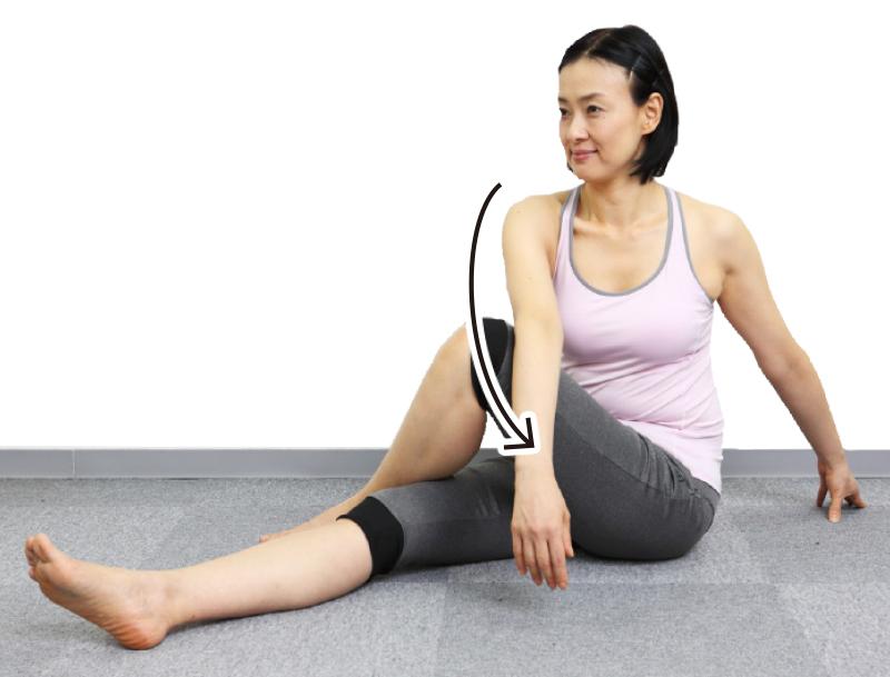 トレーニングウエア姿の女性が息を吐きながら、右手を左ひざにかけ、上体を左にスーッとひねる