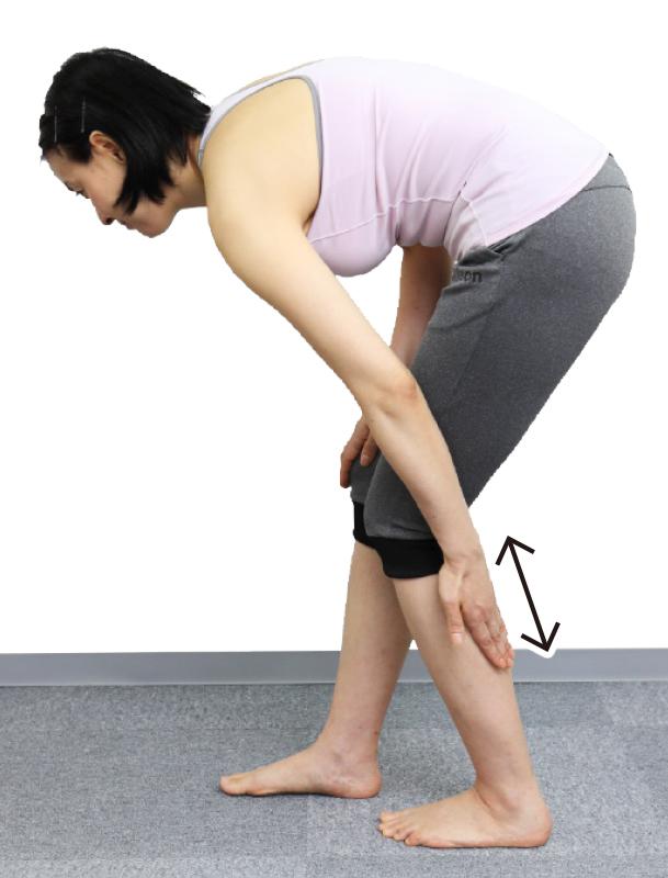 トレーニングウエア姿の女性が左足のふくらはぎの真ん中を、左手の指の腹で上下にこする