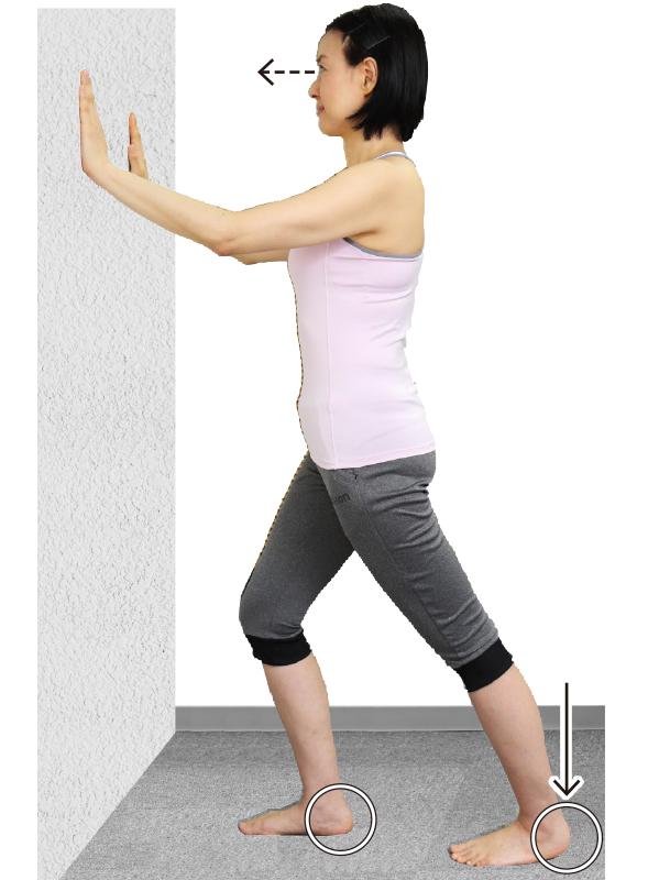 トレーニングウエア姿の女性が壁に両手をつき、右足を前にして前後に開く。つま先は正面に向け、かかとは床につける