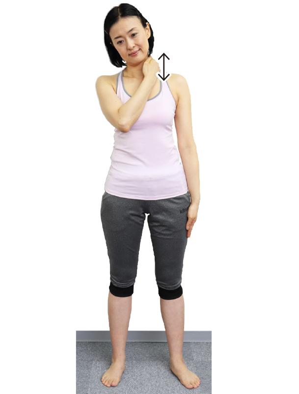 トレーニングウエア姿の女性が両足を肩幅よりやや広めに開いて立つ。頭を少し右に倒し、右手で首の左側を指の腹で上下にこする