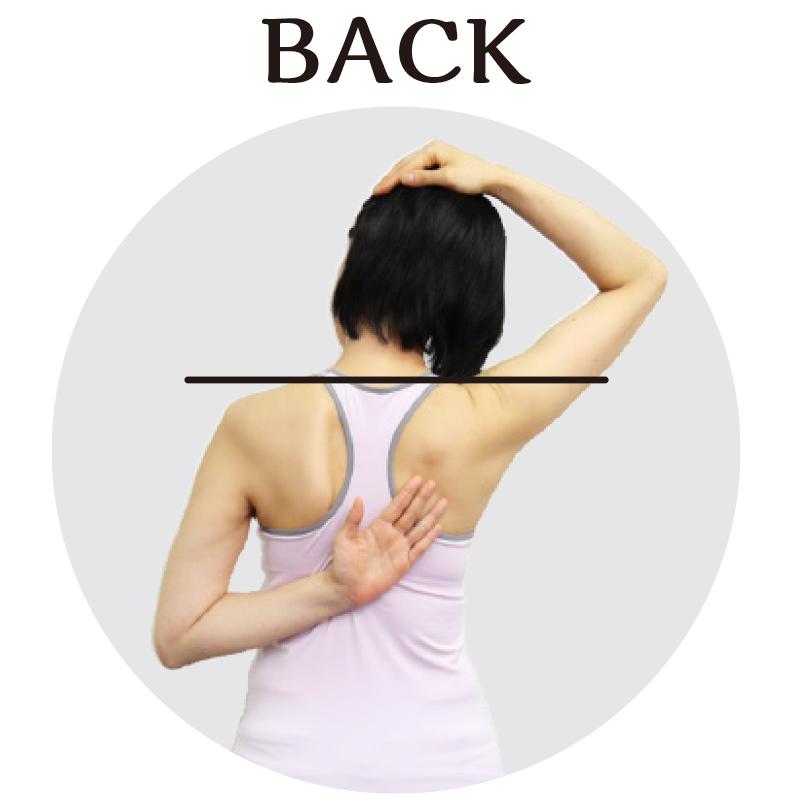 トレーニングウエア姿の女性が、頭を曲げた時に、連動して肩が上がらないように片手を背中に固定