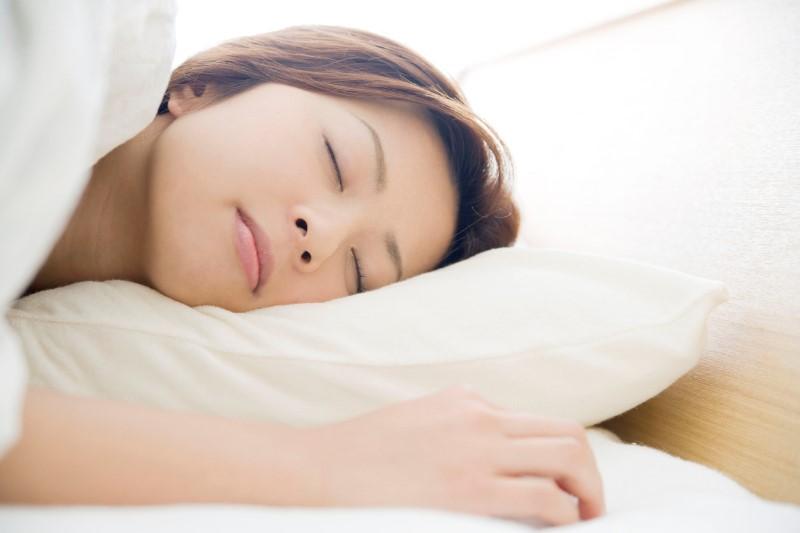 枕に頭を乗せ、横を向いて寝ている女性