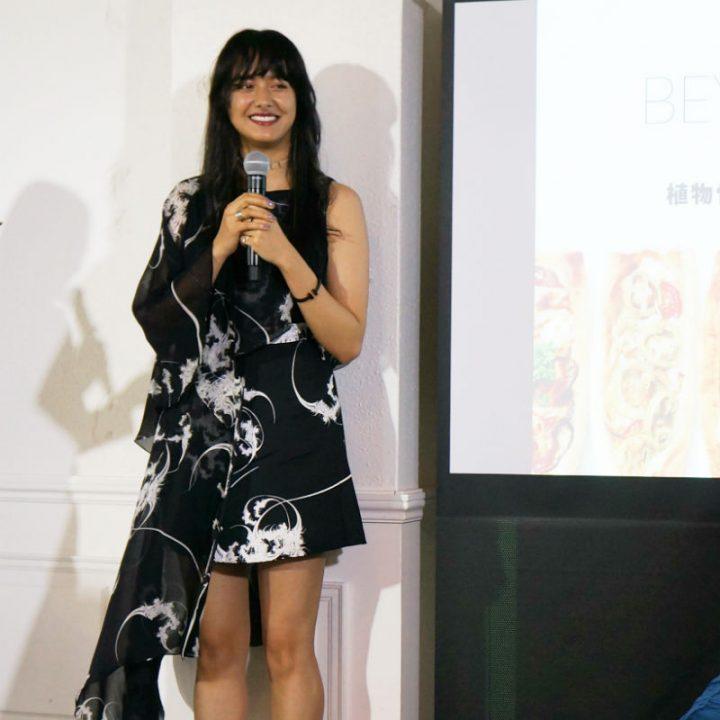 「BEYOND PIZZA」発表会に登壇した浦浜アリサさん。黒のワンピースでマイクを持っている