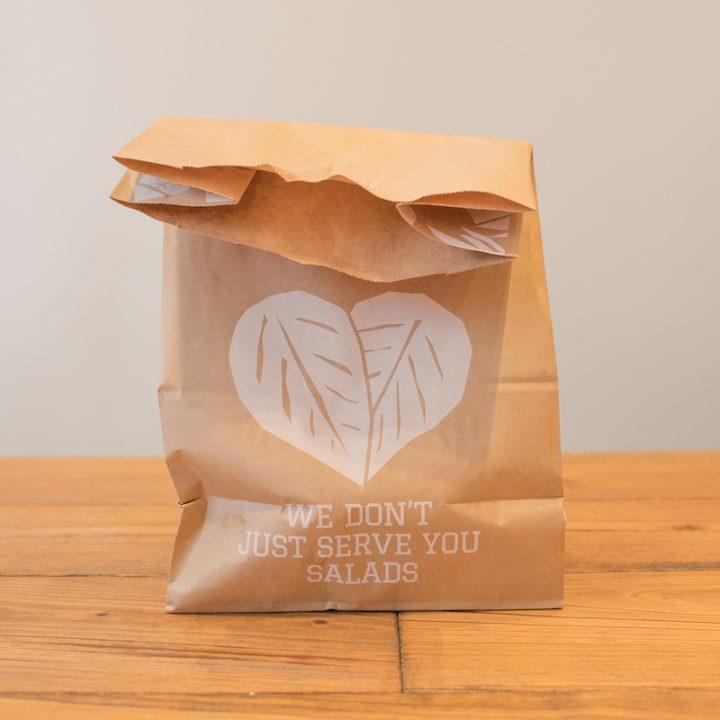 「CRISP SALAD WORKS」の葉っぱの柄が入った紙袋