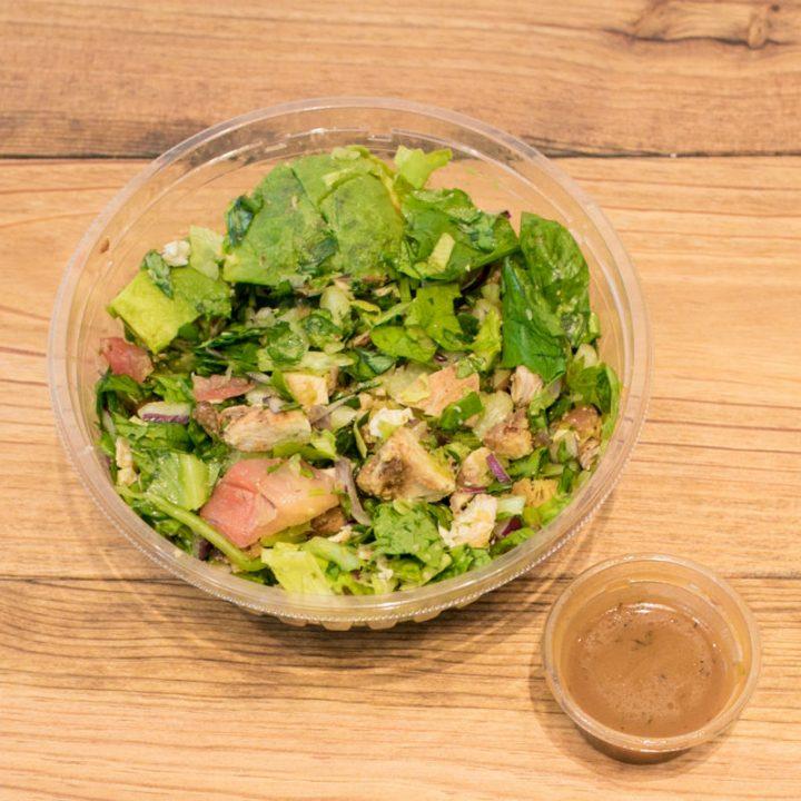 トマト、アボカド、チキンの入った「CRISP SALAD WORKS」のサラダと茶色いドレッシング