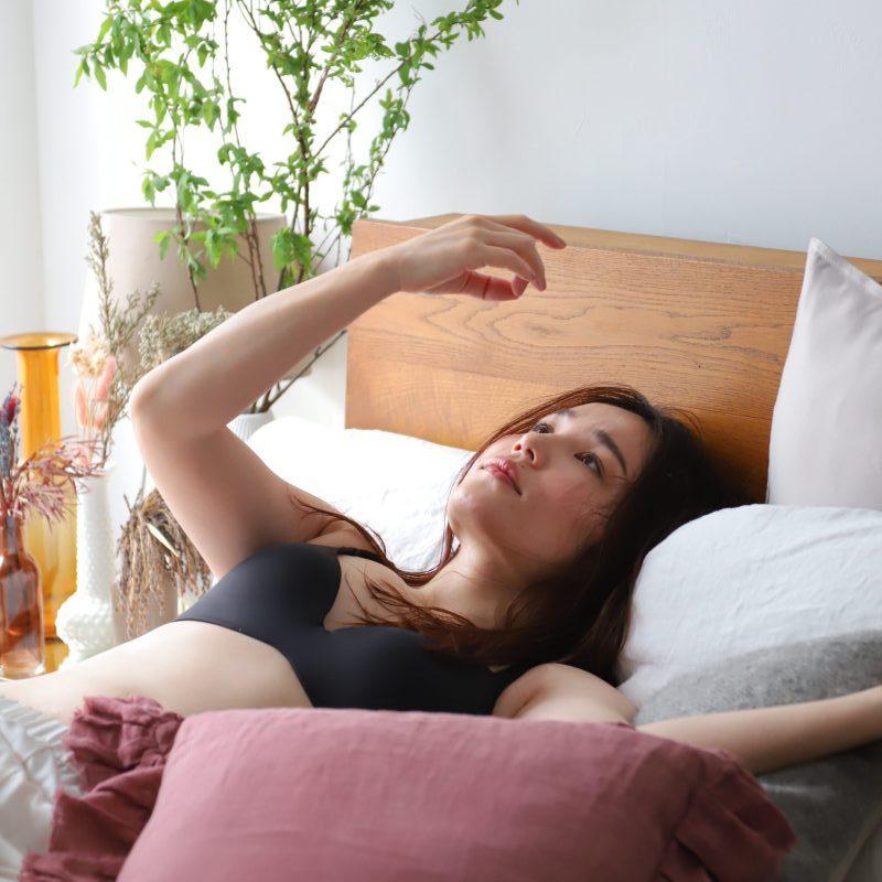 ワコールのウイング「Date.(デイト)」の新商品「シンクロブラ」を身に着け、ベッドに横たわる平野ノラ