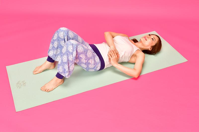仰向けになって膝を立て、両手を肋骨と骨盤の間に置く女性