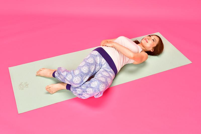 仰向けになって膝を立て、両手を肋骨と骨盤の間に置き体を左に傾ける女性